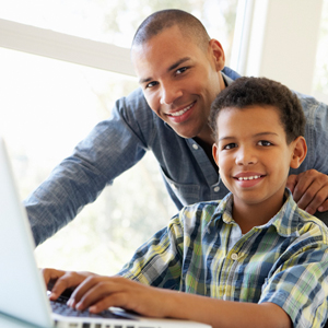 A man helping a young boy on the computer